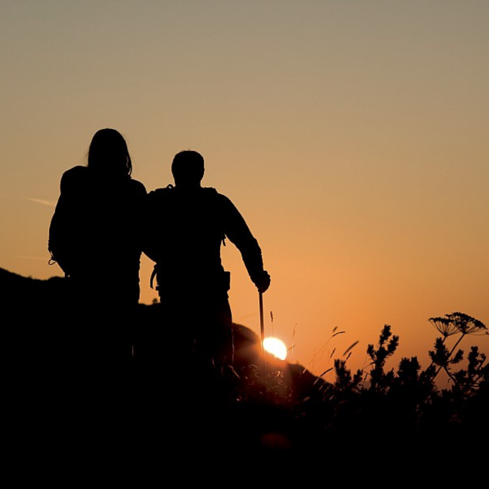 Silhouette of two people walking towards a sunset against an orange sky.