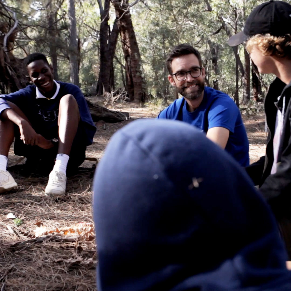 Male teacher and students sitting in a circle under some trees, smiling at each other